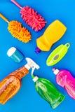 Sistema de la economía doméstica Detergentes, jabón, limpiadores y cepillo para housecleaning en maqueta azul de la opinión super foto de archivo