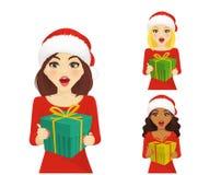 Sistema de la mujer sorprendida en el sombrero de santa de la Navidad con el regalo Imagen de archivo libre de regalías