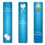 Sistema de la Navidad de la bandera azul vertical tres con las bolas de la Navidad blanca, el arco blanco y una vela ardiente Con Foto de archivo
