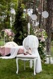 Sistema de la novia de ramo y de zapatos en la silla del vintage cubierta con velo beige del cordón al aire libre en el bosque Foto de archivo libre de regalías