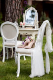 Sistema de la novia de ramo y de zapatos en la silla del vintage cubierta con velo beige del cordón al aire libre en el bosque Imagen de archivo