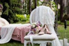 Sistema de la novia de ramo y de zapatos en la silla del vintage cubierta con velo beige del cordón al aire libre en el bosque Imágenes de archivo libres de regalías