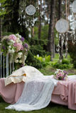 Sistema de la novia del ramo en la cama del vintage cubierta con velo beige del cordón al aire libre en el bosque Foto de archivo libre de regalías