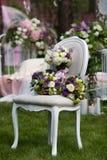 Sistema de la novia del ramo en la silla del vintage en el bosque Fotos de archivo libres de regalías