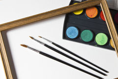 Sistema de la pintura de la acuarela, marco de madera y cepillos en el fondo blanco Imagen de archivo
