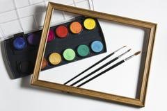 Sistema de la pintura de la acuarela, marco de madera y cepillos en el fondo blanco del álbum Foto de archivo libre de regalías
