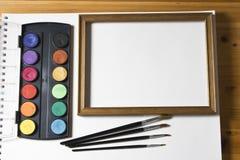 Sistema de la pintura de la acuarela, marco de madera y cepillos en el fondo blanco del álbum Fotografía de archivo
