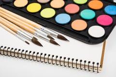 Sistema de la pintura de la acuarela y nuevos cepillos con el papel limpio Fotos de archivo