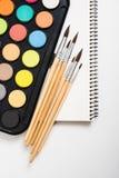 Sistema de la pintura de la acuarela y nuevos cepillos con el papel limpio Imagen de archivo libre de regalías