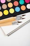 Sistema de la pintura de la acuarela y nuevos cepillos con el papel limpio Imágenes de archivo libres de regalías