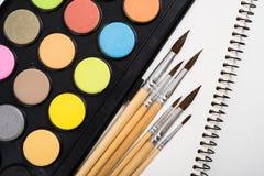 Sistema de la pintura de la acuarela y nuevos cepillos con el papel limpio Foto de archivo libre de regalías