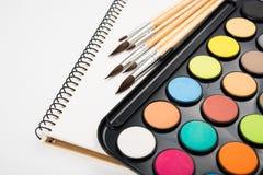 Sistema de la pintura de la acuarela y nuevos cepillos con el papel limpio Imagen de archivo