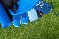 Sistema de la ropa de deportes azul para entrenar, en un bolso, en el fondo de la hierba Imagenes de archivo