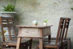 Sistema de la tabla de madera y de la silla adornadas en jardín Imágenes de archivo libres de regalías