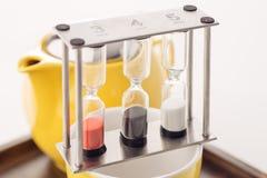 Sistema de la tetera con los relojes y té flojo en un envase en el fondo blanco, producto para el salón de té Fotos de archivo