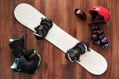 Sistema de las botas, del casco, de los guantes y de la máscara de la snowboard en de madera Fotos de archivo libres de regalías