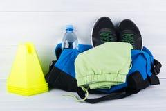 Sistema de las cosas de los deportes para jugar deportes, zapatillas deportivas y una forma en un bolso y una botella de agua, al Foto de archivo libre de regalías