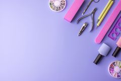 Sistema de las herramientas cosméticas para la manicura y la pedicura en un fondo púrpura Pulimentos del gel, ficheros de clavo y Foto de archivo