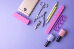 Sistema de las herramientas cosméticas para la manicura y la pedicura en un fondo púrpura Pulimentos del gel, ficheros de clavo y Fotos de archivo libres de regalías