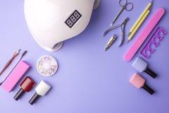 Sistema de las herramientas cosméticas para la manicura y la pedicura en un fondo púrpura Pulimentos del gel, ficheros de clavo y Fotografía de archivo