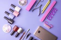 Sistema de las herramientas cosméticas para la manicura y la pedicura en un fondo púrpura Pulimentos del gel, ficheros de clavo y Foto de archivo libre de regalías