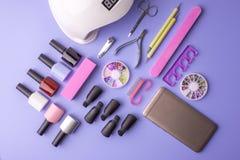 Sistema de las herramientas cosméticas para la manicura y la pedicura en un fondo púrpura Pulimentos del gel, ficheros de clavo y Fotografía de archivo libre de regalías