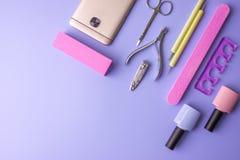 Sistema de las herramientas cosméticas para la manicura y la pedicura en un fondo púrpura Pulimentos del gel, ficheros de clavo y Imagen de archivo libre de regalías