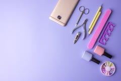 Sistema de las herramientas cosméticas para la manicura y la pedicura en un fondo púrpura Pulimentos del gel, ficheros de clavo y Imagen de archivo
