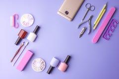 Sistema de las herramientas cosméticas para la manicura y la pedicura en un fondo púrpura Pulimentos del gel, ficheros de clavo y Imagenes de archivo