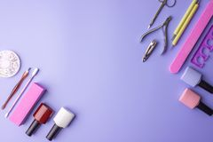 Sistema de las herramientas cosméticas para la manicura y la pedicura en un fondo púrpura Pulimentos del gel, ficheros de clavo y Fotos de archivo