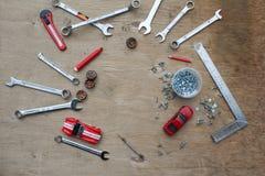 Sistema de las herramientas para el coche que repara en fondo de madera con los coches rojos del juguete del contraste Visión sup Imágenes de archivo libres de regalías