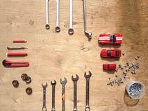 Sistema de las herramientas para el coche que repara en fondo de madera con los coches rojos del juguete del contraste Visión sup Imagen de archivo