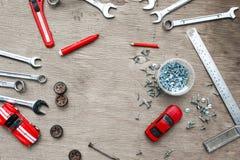Sistema de las herramientas para el coche que repara en fondo de madera con los coches rojos del juguete del contraste Visión sup Imagen de archivo libre de regalías