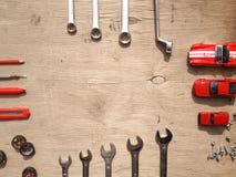 Sistema de las herramientas para el coche que repara en fondo de madera con los coches rojos del juguete del contraste Visión sup Imagenes de archivo