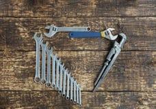 Sistema de las llaves combinadas y de las llaves ajustables viejas en un viejo fondo de madera Fotografía de archivo libre de regalías