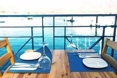 Sistema de las placas y de los cubiertos en la tabla de madera en el restaurante con la vista al mar en el fondo Fotos de archivo libres de regalías