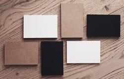 Sistema de las tarjetas blancas, negras y del arte de visita en la tabla de madera Visión superior horizontal Fotos de archivo libres de regalías