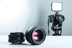 Sistema de lentes de DSLR en una tabla blanca en stuidio, contra la perspectiva de la cámara de DSLR a encenderse y del softbox fotos de archivo