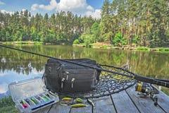 Sistema de los aparejos de pesca Barra de giro con el carrete y señuelos en la plataforma de madera en fondo del lago del bosque Fotos de archivo
