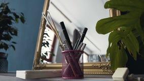 Sistema de los cepillos para el maquillaje en el espejo cercano de la tabla en el sitio Sistema de cepillo para el maquillaje en  almacen de metraje de vídeo