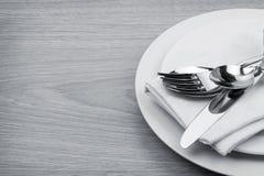 Sistema de los cubiertos o de los platos y cubiertos de la bifurcación, de cucharas y del cuchillo en la placa Foto de archivo