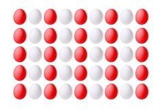 Sistema de los huevos blancos y rojos en un fondo blanco, puesto en líneas verticales Primer Fotografía de archivo