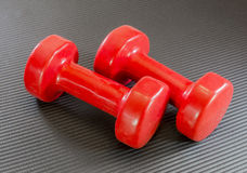 Sistema de los pesos rojos de la mano, pesas de gimnasia, mintiendo en un yo negro del ejercicio Imagen de archivo libre de regalías