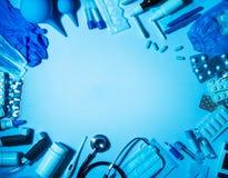 Sistema de medicinas y de dispositivos de los primeros auxilios en casa, en azul Imagenes de archivo