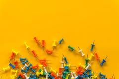 Sistema de pernos del empuje en diversos colores thumbtacks Visi?n superior En fondo amarillo imagen de archivo