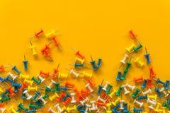 Sistema de pernos del empuje en diversos colores thumbtacks Visi?n superior En fondo amarillo foto de archivo libre de regalías