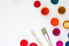 Sistema de pinturas brillantemente coloreadas con los cepillos en la opinión superior del backround blanco de la tabla Fotografía de archivo libre de regalías