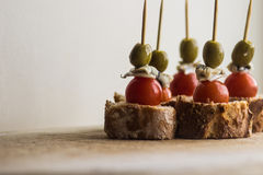 Sistema de Pintxos Pintxo, aceituna, anchoa, tomate de cereza y pan en un tablero rústico, comida del país vasco Foto de archivo