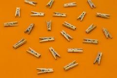 Sistema de pinzas de madera en fondo anaranjado Imagen de archivo