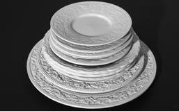 Sistema de placas de cerámica blancas hermosas del alivio de la cena en fondo negro imagen de archivo